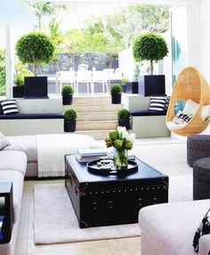 White walls + pale wood floor + white couches + white rug + trunk table + blue accents = the living room, love how it opens to outdoors