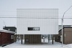 CYIN is a minimalist residence located in Hokkaido, Japan, designed by archi LAB. The wooden house is cantilevered, lifting the larger volume above a smaller wooden volume. A large rectangular window is placed toward the back of the building, away from the street in order to maintain privacy while allowing abundant natural lighting to enter the spaces within. The interior is composed mainly of exp