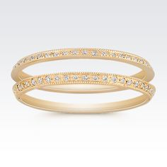 Crafted from superior quality 14 karat yellow gold, this vintage-inspired design features two bands.  Forty-six round pavé-set diamonds, at approximately .05 carat total weight, are surrounded by a milgrain design.  These gorgeous rings can be worn on either side of your engagement ring to add a unique new look.