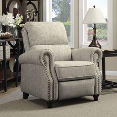 The ProLounger wall hugger recliner is covered in a linen-like barley tan fabric. Sit back and relax in this rounded arm reclining chair accented with hand-tacked antique bronze nail heads.
