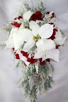 Dans un style plus classique, ce bouquet regroupe de nombreux code de Noël : la blancheur de la neige qu'on retrouve dans les fleurs, le rouge du Père Noël, les tiges de sapin presque glacés et la pomme de pain.