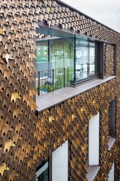 A private home in Mayfair, London gets a striking new exterior in the form of over 4,000 folded aluminum leaves in various shades of bronze.  Architects: Squire and Partners
