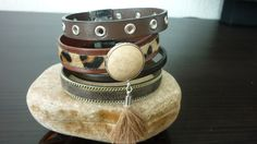 Armband van Eco Nappa with Rings, Brown Flat leather, Brown Nature leather on leather, small dark brown leather en Brown Leather with Metalic effect and Silver chain along the border , leerschuiver met Polariscabochon en kwastje en magneetsluiting.  € 25,=