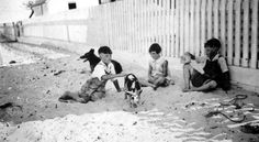"""Playing with the pet pig """"Alice"""" on the beach (ca. 1930). 