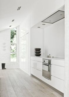 white lacquered kitchen with gray wood floors and white walls