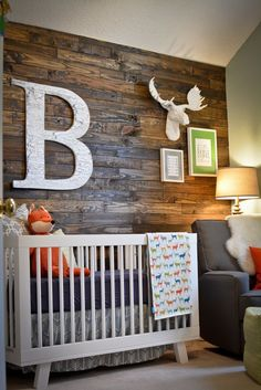 Rustic woodland nursery featuring a reclaimed wood accent wall - so chic!