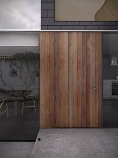 I love the combination of materials and extension of wood to the left of the door. Also, framless.