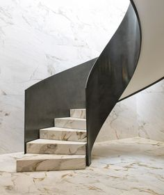 Renderings of Starck's interiors show the use of local materials including marble quarried from the Brazilian states of Paraná and Bahia. A twisting marble and Corten-steel staircase is depicted as it sweeps down onto the marble floor.