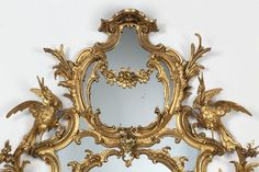 Chippendalemirrorin an elaborate, oval frame of carved and gilt wood formed of symmetrical scroll-work. Great Britain, UK