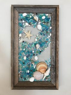 This is a handmade, one of a kind, sea glass/beach glass art piece. The frame is made from barnwood. Please Keep in mind with barnwood frames- they are made from real barns so some wood has rusted nail holes, and imperfections that only add to their charm. The photo represents the exact