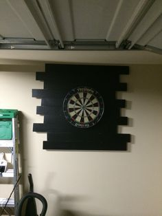 Dart board backing  3, 12 foot treated wood planks cut down to 3 foot planks... Sanded, primer + adhesive, and painted flat black. Off set then hung in the cave! Works and looks great!
