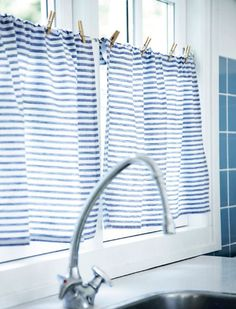 The perfect styling detail from a Danish Summer House - blue and white striped curtains with simple pegs holding them in place