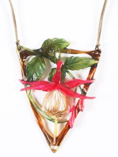 An Art Nouveau carved horn pendant by Elizabeth Bonte. It depicts a white flower bud with yellow stigmas. Surrounding the bud are painted fushia sepals on a stem of green leaves. The pendant's triangular frame is suspended from a beige cord with red carved-horn and green-paste bead spacers.