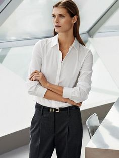 A white button-down shirt is worn with pleated gray pants and a leather skinny belt