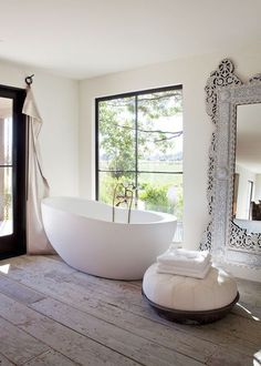 bath time in such house with a view like this is a treat! Egg shape tub, ultra wide plank flooring, antique Indian mirror, all white color