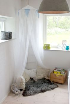 "mosquito net forms a lovely reading corner with pillows on the floor...for Miller's room, ""quiet corner"""