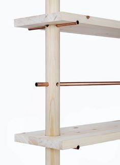 Une plaque est ancrée dans un bout de bois, elle ne glisse pas vers le bas grâce à des tuyaux passant à travers celui-ci en dessous de cette même plaque.