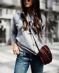 A Calvin Klein sweater with jeans and a crossbody bag.