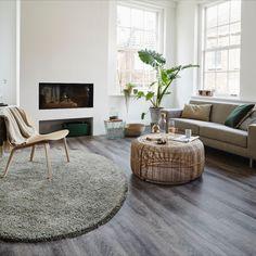 Het voordeel van een voerkleed is dat je ook nog de prachtige vloer ziet die eronder zit. Met een rondvloerkleed geef je je woning een knusse sfeer. En deze donker grijze pvc-vloer maakt het helemaal af. #dessotarkett #watisjouwstijl #pvcvloer #rondvloerkleed #vloerinspiratie #donkerevloer Natural Living, Ottoman, New Homes, Room Decor, Living Room, Chair, Bedroom, Table, Cheryl