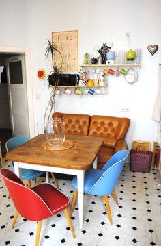 Eclectico y colorido, con un marcado aire retro. Buena idea la de usar el sofá como asiento de comedor. Con este mobiliario se destaca adecuadamente el piso.