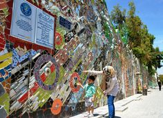 """""""World's biggest mural made of street scraps in Damascus. A mother and her boy look at a decorated wall, recognized by the Guinness World Records as the world's largest mural made of recycled materials, in the civil war-ravaged Syrian capital of Damascus on May 15, 2014. (Kyodo)"""""""