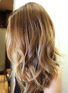 Une longue chevelure aux pointes légèrement ondulée dans laquelle on distingue des mèches colorées de différentes nuances de châtain.