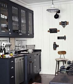 Embrace contrast  Honed black-granite countertops and black-painted oak cabinets offer a dramatic counterpoint to this kitchen's white plank walls. Plumbing-pipe fittings make for unexpected wall art.