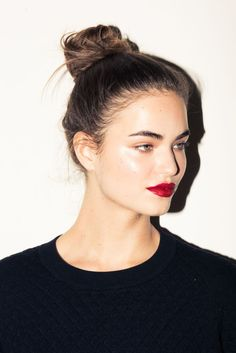 can't go wrong with pretty highlighter, a bold red lip and a perfect top knot hairstyle   thecoveteur.com