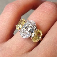 Bespoke three stone oval engagement ring with a Colorless oval center diamond and Fancy Yellow matching side diamonds.