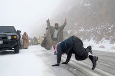 People play after a heavy snowstorm in the desert near Tabuk, Saudi Arabia
