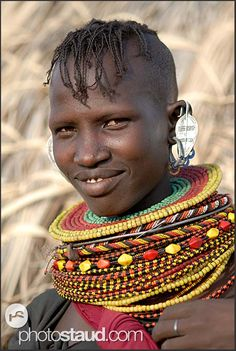 Smiling Turkana girl with traditional hairstyle and bead necklaces, Loyangalani, Northern Kenya