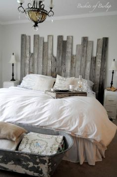 Soft grey walls, rustic headboard made with recycled barn wood and cowboy tub at the end of bed. Love this DIY master bedroom has a rustic, yet romantic feel.