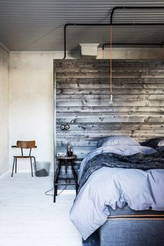 Swedish bedroom with a reclaimed wood wall, a pendant light and textured throw blankets