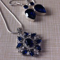 Stunning elegant tanzanite SET white Cz 925 NWOT Stamped bail 925 this is super sparkling piece 8 stones surrounded by a bigger one pendant is almost 1/5 inches long including bail stones is lab created  overlay size is 8/6 mm and 6/3 mm a beautiful pendant free chain and earrings stamped 925 with purchase Jewelry