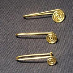 First generation spiral safety pins, brass.