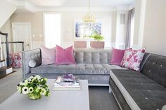 Gorgeous contemporary living room with light gray colored walls is clad in a gray geometric area rug sat beneath a gray velvet Jonathan Adler Lampert Sectional topped with blush pink velvet pillows and blue and pink printed pillows positioned in front of a gray coffee table.