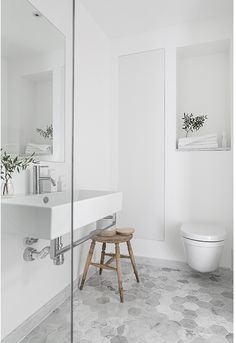 I really like the subtly rustic-modern look of the stone-like tiles and the wood stool.