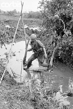 """4 Jan 1966, Mekong Delta, South Vietnam. Paratroopers of the 173rd Airborne Brigade cross a small muddy stream typical of the operational area of the Mekong Delta near the Cambodian Border where the troops are stationed."