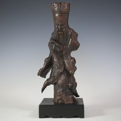 "DESCRIPTION: Antique Chinese wood sculpture of the Chinese deity of longevity. Seen here with a carved head piece and long flowing beard. Tapers down to an abstract flowing body. CIRCA:19th|20th Ct. ORIGIN:China DIMENSIONS:H:10"" L:4.5"""