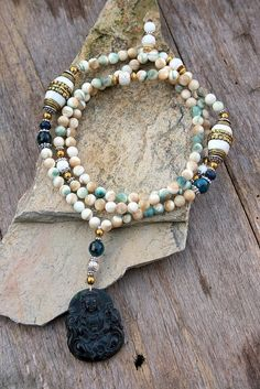 Beautiful Mala necklace made of 108, 8 mm - 0.315 inch, shell stones and decorated with two nepalese beads, engraved shell beads, faceted agate and a black jade Kwan Yin pendant - Made by look4treasures