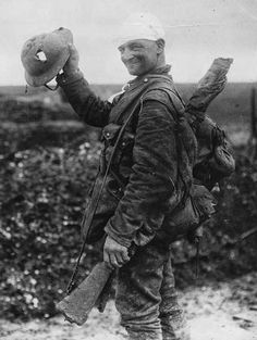 WWI British solider showing of the hole in his helmet, 1917