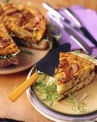 Spanish Onion and Potato Torta    A traditional Spanish tortilla rests on top of a toasted loaf of bread. A lightly dressed frisee salad is sandwiched in the middle.