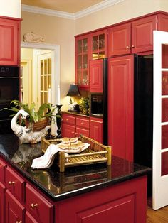 Red cabinets with black granite counter tops