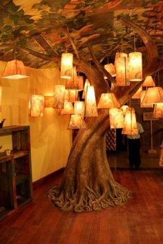 Indoor faux tree with lamps hanging all over.
