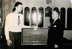 A member of the Varsity crew receives the first annual Clifford 'Tip' Goes award at the Block S Dinner c. 1940. On the wall in the back are plaques listing past recipients of the Block 'S'. Clifford 'Tip' Goes Award Bestowed, c. 1940. (Syracuse Archives) #PreppySyracuse