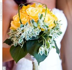 Alexis carried a beach-worthy bouquet of yellow roses framed by greenery, with stems of sea grass shooting up over the top.