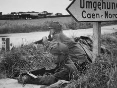 British paratroopers near Caen in Normandy just after D-Day (ca. June 1944). Notice the German sign pointing toward Caen, and the glider visible on a field in the background. Both soldiers appear to be armed with Sten guns, with the soldier in front issued the newest MkV.