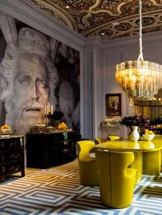 The oversized neoclassical style mural tops off a dramatic light fitting and modernist acidic yellow chairs. #Interiors #Inspiration