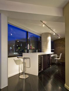The triangular second balcony space that had already been incorporated into interior space by the previous owners now houses a wet bar that engages the concrete column on one side and a study area on the other side of the column.