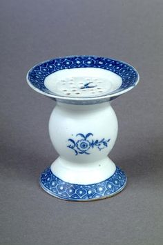 Porcelain Pounce Pot c.1780-1790. Pounce is a fine powder sprinkled over wet ink to hasten drying prior to the invention of blotting paper. The powder was prepared from substances such as finely ground salt, sand, cuttlebone, or powdered soft minerals such as talc or soapstone. Many pounce pots have concave lids to make it easier to return spare pounce to the pot.